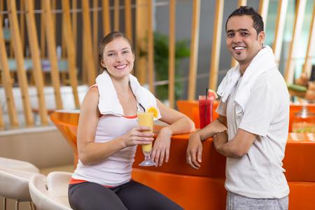 Jonge vrouw en man het dragen van sportkleding, het drinken van smoothies in heldere sport bar na de training en lacht naar de camera. Gezonde leefstijl concept