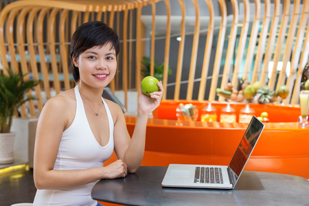 Smiling young Asian woman wearing sport clothes, sitting at table with laptop in fitness cafe, holding fresh apple and smiling at camera
