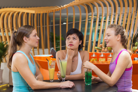 happy asian people: Three young women wearing sport clothes, sitting at table in modern sport cafe, drinking smoothies and talking after training