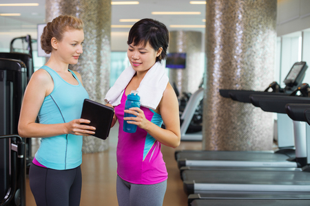 computer club: Two young sporty women wearing sport clothes, standing in cardio room of modern fitness club and using tablet computer. Trainer showing progress results to sportswoman with bottle of water