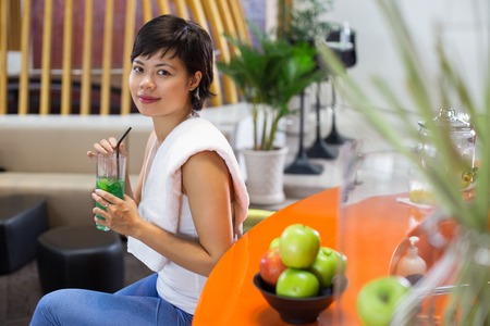 Young Asian woman with towel on shoulder, sitting in sport bar, drinking refreshing cocktail and smiling at camera Stock Photo