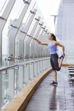 legs open: Portrait of young Caucasian woman doing exercises on open terrace of modern fitness club, stretching her legs. Fitness concept