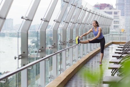 legs open: Young Caucasian woman doing stretching exercises on open terrace of modern sport gym, stretching her legs. Healthy lifestyle concept