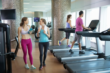 two women and one man: Two smiling young women chatting, relaxing, wearing sportswear and walking in gym. One woman is holding bottle of water. Another woman and man are training on treadmills. Full length view. Stock Photo