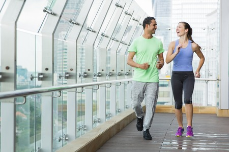 Glimlachende en lachende jonge man en vrouw die sportkleding en jogging op terras met glasomheining en mening van stad buiten dragen
