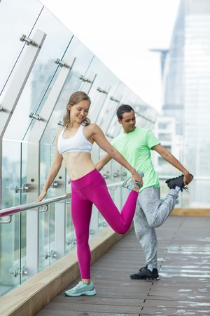 simultaneously: Smiling young woman and man wearing sportswear, standing and stretching legs simultaneously on terrace with glass fence and blurry view of city outside