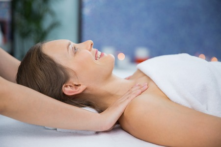 masseuse: Close up of smiling young woman lying and enjoying neck and collar area massage and masseuse hands in spa salon room. Side view.
