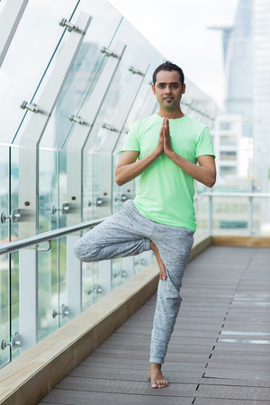 Smiling at camera young man wearing sportswear, doing yoga, standing on one leg in tree pose, pressing hands together in Namaste on balcony with glass fence and blurry city view outside. Full length.