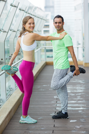 simultaneously: Smiling at camera young woman and man wearing sportswear, standing, holding on to each other and stretching legs simultaneously on terrace with glass fence and blurry view of city outside