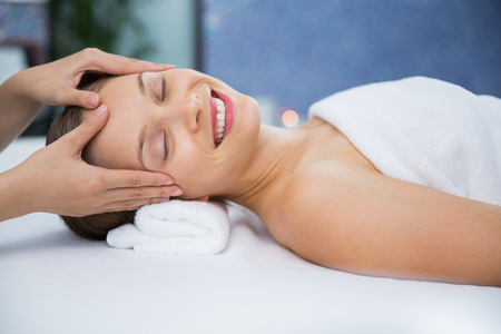 eyes closing: Close up of smiling young woman lying, closing her eyes and enjoying facial massage and masseuse hands in spa salon room. Side view.
