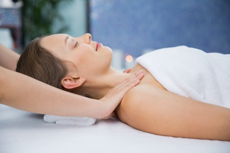 masseuse: Close up of content young woman lying, closing her eyes and enjoying neck and collar area massage and masseuse hands in spa salon room. Side view.