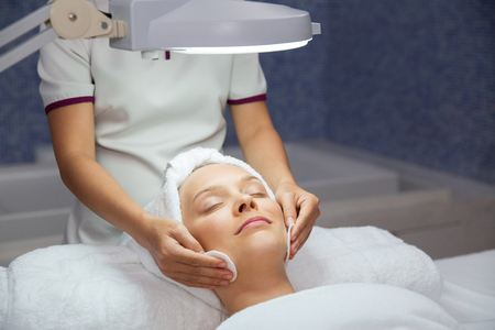 eyes closing: Close up of young woman lying under lamp, closing her eyes and having cleaning facial treatment and masseuse hands in spa salon room