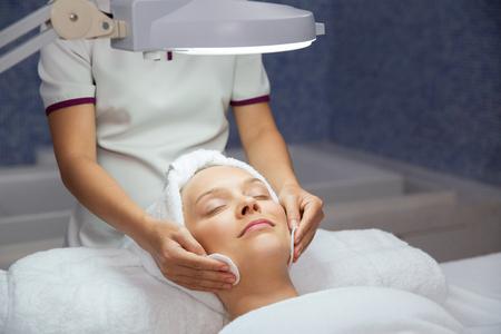 pulizia viso: Primo piano di giovane donna che si trova sotto la lampada, chiudendo gli occhi e con la pulizia di trattamento e massaggiatrice mani del viso in spa stanza salone