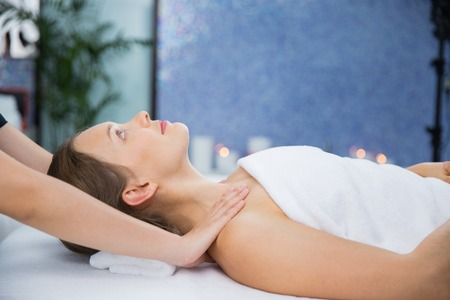 masseuse: Close up of content young woman lying and having neck and collar area massage and masseuse hands in wellness center. Side view.