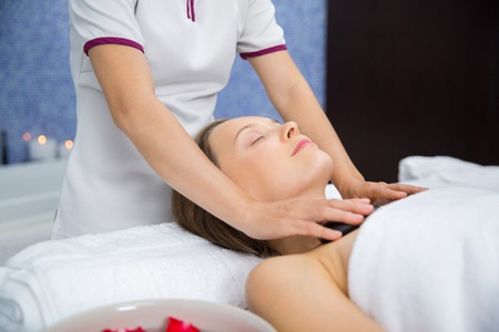 eyes closing: Content young woman closing eyes, lying on table and having stone massage therapy of chest in spa salon room Stock Photo