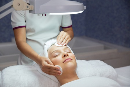 eyes closing: Close up of content young woman lying under lamp, closing her eyes and having cleaning facial treatment and female therapist hands in spa salon room