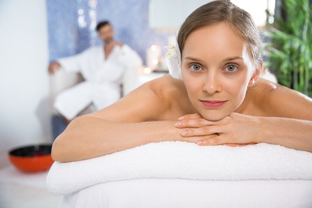 Close up of slightly smiling at camera young woman lying on massage table and blurred man wearing bathrobe and sitting relaxedly behind in spa salon. Front view. Stock Photo