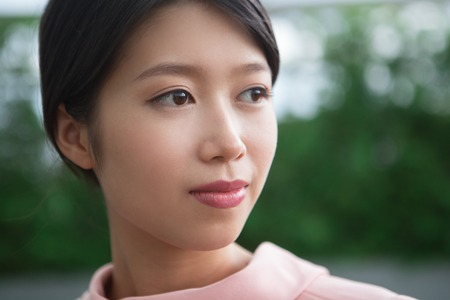 looking aside: Closeup portrait of beautiful content young Asian woman looking aside with blurry green background