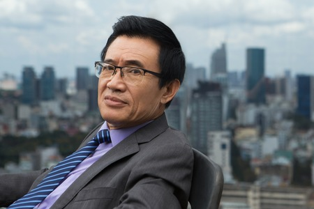 Closeup portrait of content Asian senior businessman sitting in armchair, turning his face and looking at camera with city view in background. Side view.