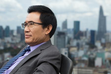 Sluit omhoog portret van nadenkende Aziatische hogere zakenmanzitting in leunstoel en kijkend opzij met stadsmening op achtergrond. Zijaanzicht.