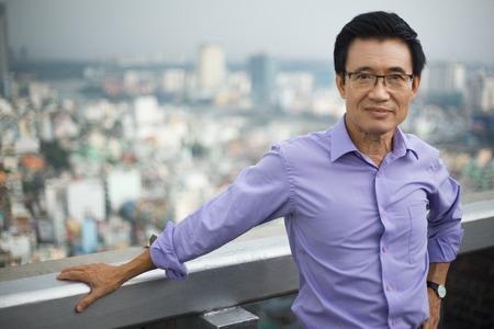 Portret van de zekere Aziatische hogere mens die camera bekijkt en zich met stadsmening bevindt op achtergrond Stockfoto
