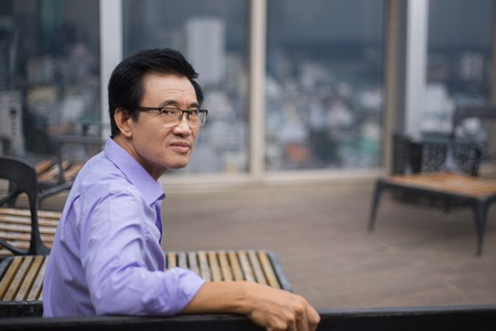 window bench: Portrait of serious Asian senior man looking at camera and sitting on bench in cafe with city view outside window in background. Side view.