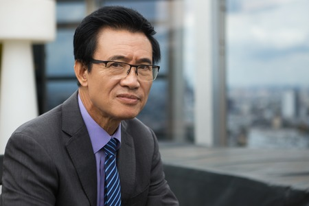 Closeup portrait of thoughtful Asian senior businessman looking at camera with blurry city view in background Stock Photo