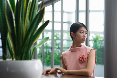 aside: Portrait of worried young Asian woman looking aside and sitting at table in cafe with plant in foreground