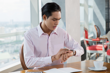 watch city: Portrait of worried young Asian man looking at watch and sitting at table in cafe with blurry city view outside window and chairs in background Stock Photo