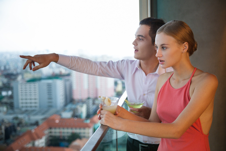 Young man pointing and showing something to woman. They are holding cocktails and standing on balcony with city view outside.