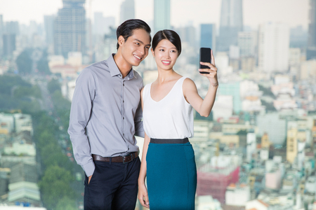ropa casual: Young Asian couple standing in background with city view, smiling and taking selfie photo with smartphone