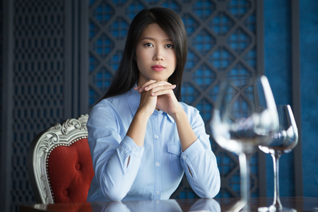 chin on hands: Portrait of pretty young Asian woman with her hands under chin sitting at table in luxury restaurant, looking at camera