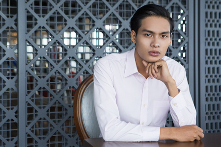 waiting glance: Portrait of serious young Asian businessman with hand under chin sitting in restaurant and looking at camera