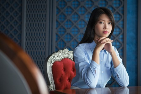 chin on hands: Portrait of pretty young Asian woman with her hands under chin sitting in luxury restaurant, looking at camera Stock Photo