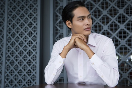 chin on hands: Portrait of serious young Asian businessman with his hands on chin sitting in restaurant, looking away Stock Photo