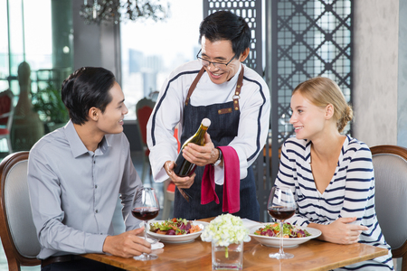 addressing: Happy young couple sitting at table in restaurant, smiling Asian waiter offering bottle of red wine, addressing to man Stock Photo