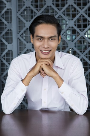 chin on hands: Portrait of young Asian businessman sitting in restaurant, holding his hands under chin, smiling at camera