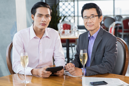 professional flute: Two confident Asian businessmen sitting with glasses of champagne in restaurant, discussing business project, looking at camera Stock Photo