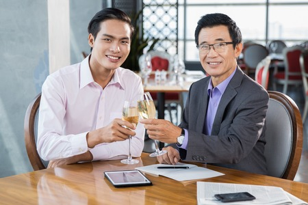 professional flute: Two Asian business partners sitting in restaurant, drinking champagne, celebrating success, looking at camera and smiling
