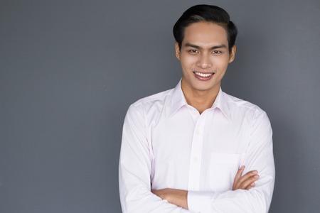 Portret van jonge Aziatische zakenman die zich met gekruiste wapens bevindt, die bij camera glimlacht