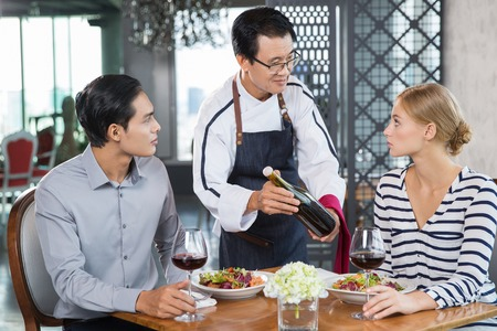 informal clothes: Young couple sitting at table in restaurant, middle-aged Asian waiter offering them bottle of red wine