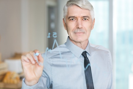 Closeup portrait of content senior businessman looking at camera and drawing graph on transparent glass and standing behind it with blurry office interior in background
