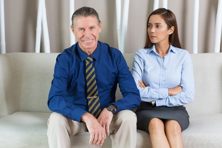 leaning on elbows: Smiling at camera senior businessman leaning elbows on knees and sitting on sofa next to serious young female colleague looking at him with arms crossed.