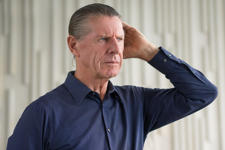 tensed: Portrait of thoughtful frown serious man holding his hand on head, looking away Stock Photo