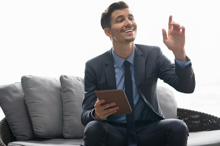 addressing: Portrait of successful young businessman wearing suit, sitting in cafe, holding tablet computer, calling waiter with hand gesture Stock Photo