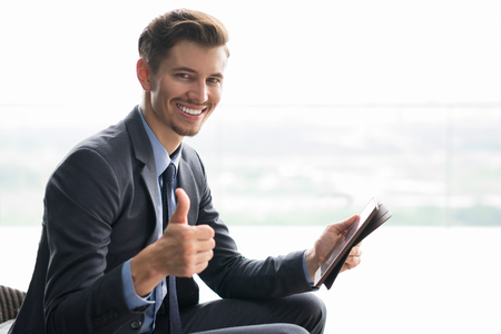 thump: Portrait of smiling at camera young businessman showing thump up, holding tablet and sitting in cafe in front of window with light view outside. Side view. Stock Photo