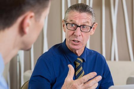 Close-up van verbaasde senior zakenman gebarend, praten en kijken naar jonge partner die gedeeltelijk wordt gezien