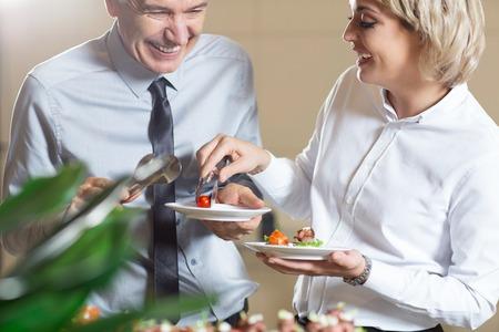 Twee gelukkige bedrijfsmensen die dienen in buffet van restaurant. Vrouw die de mens helpt om snack op plaat te zetten. Catering concept