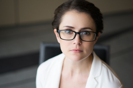 Closeup portrait of looking at camera serious sincere beautiful middle-aged woman wearing glasses and jacket