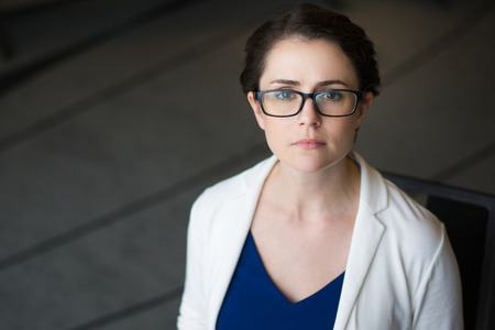 Closeup portrait of looking at camera serious strict beautiful middle-aged woman wearing glasses and jacket while sitting on chair Stock Photo